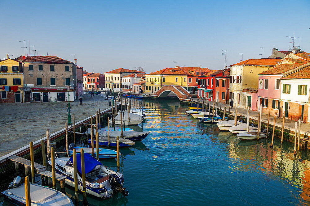Murano, Italy view of Ponte San Martino stone bridge over canal with colorful buildings & moored boats on wooden wharf pilings. - 1278-218