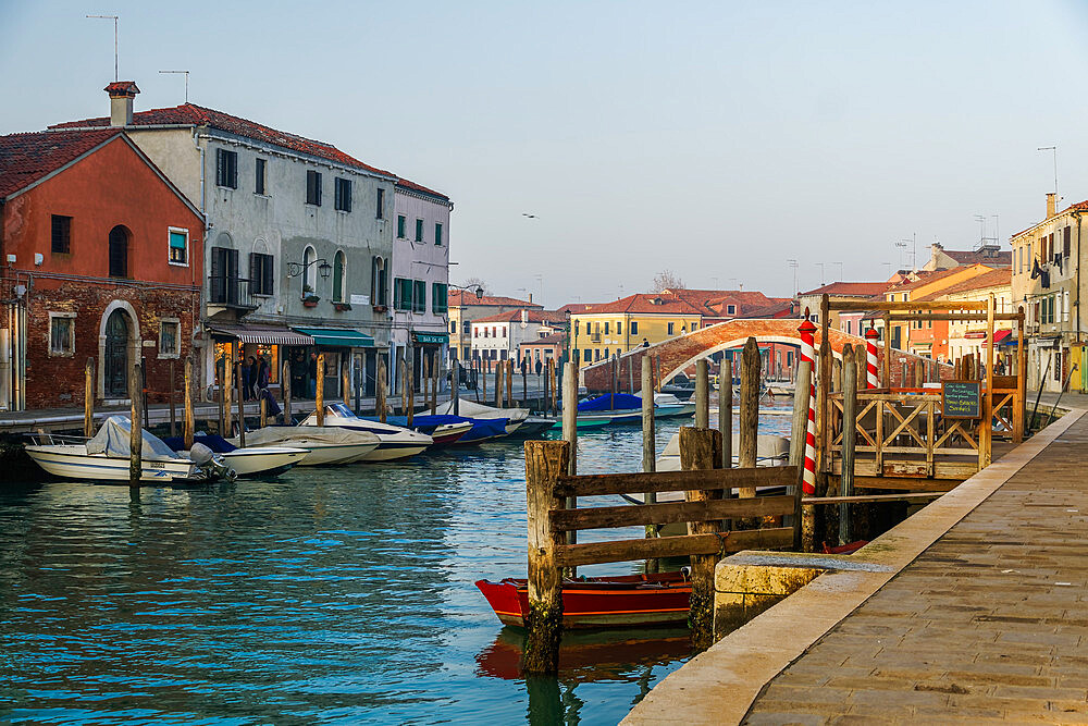 Murano, Italy view of Ponte San Martino stone bridge over canal with colorful buildings & moored boats on wooden wharf pilings. - 1278-219