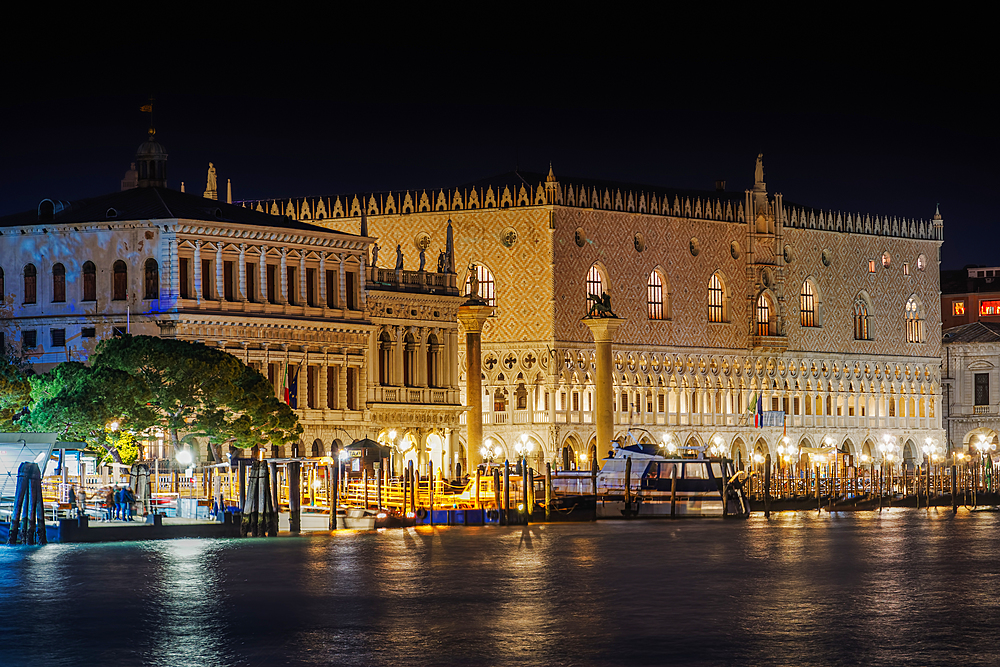 Venice Italy night view of illuminated Palazzo Ducale, Doges Palace facade with Columns at St. Marks square, seen from Dorsoduro