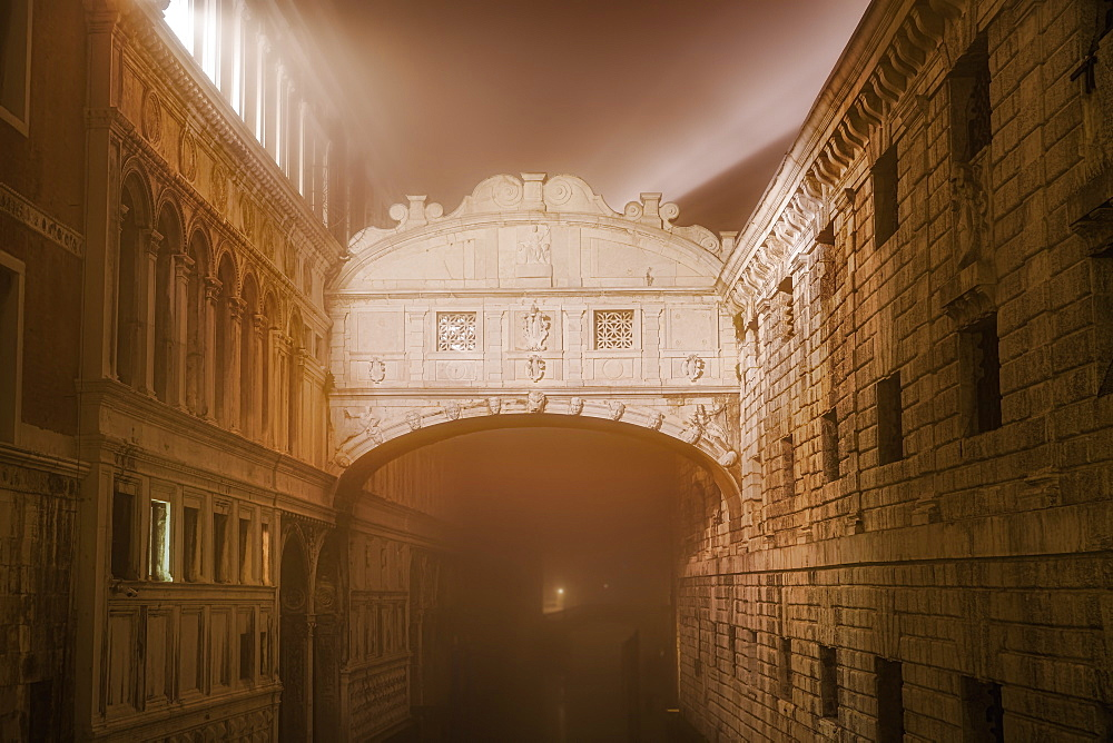 Venice, Italy foggy view without crowd of Ponte de Sospiri, iconic Bridge of Sighs stone bridge at night.
