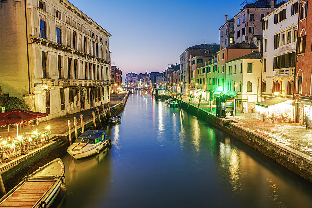 Venice, Italy evening canal view of low rise traditional buildings and wooden wharf pilings with moored boats.