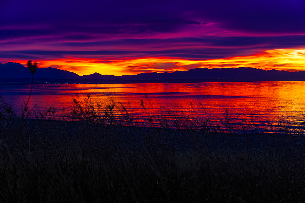 Mediterranean sunset over calm sea, orange and purple clouds over mountainous landscape silhouette, Greece, Europe