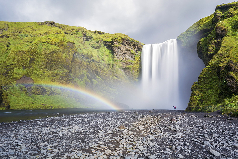 Double rainbow and tourists with hands in the air at Skogafoss waterfall in South Iceland, Polar Regions