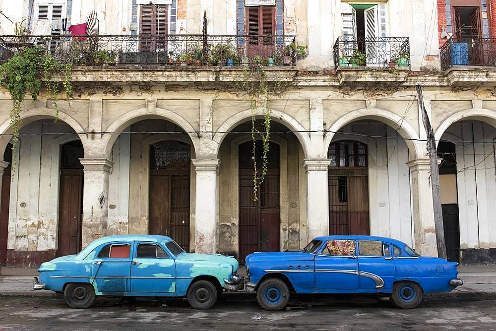Two blue cars face nose to nose outside a dilapidated building, Havana, Cuba, West Indies, Caribbean, Central America