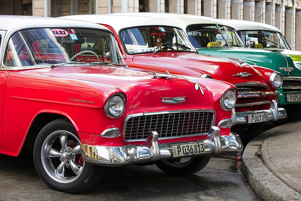 Red and green vintage American cars parked in a taxi rank near the train station. Havana, Cuba, West Indies, Caribbean