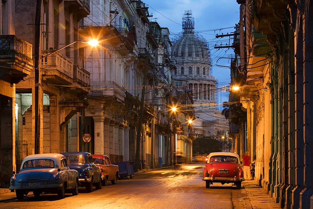 Old American vintage cars on a Havana street near El Capitolio building at dawn. Cuba, West Indies, Caribbean, Central America