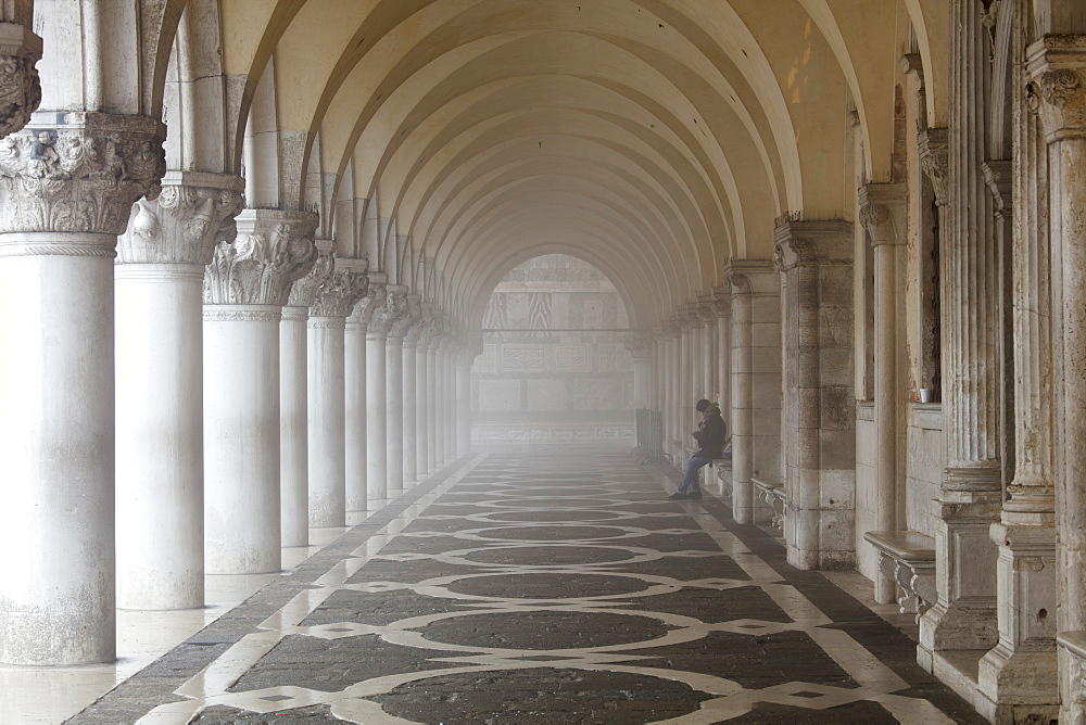Misty view of pillars with lone woman sitting, Doge's Palace, St. Mark's Square, Venice, UNESCO World Heritage Site, Veneto, Italy, Europe