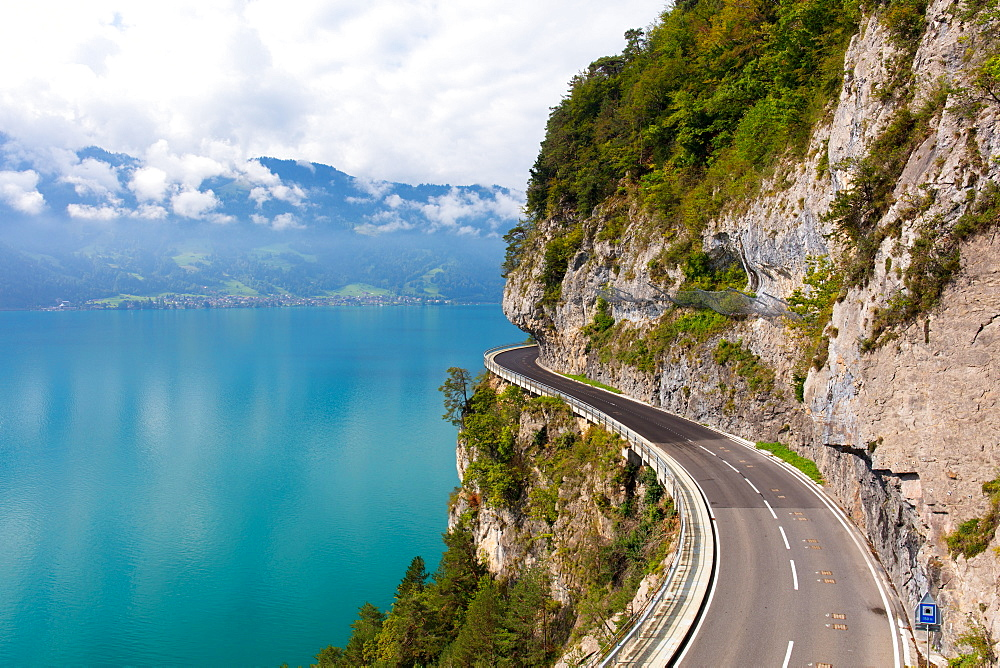 A curved road built into the side of a mountain next to Lake Thun, Interlaken, Bernese Oberland, Bern, Switzerland, Europe - 1284-180