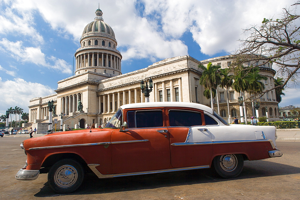 A red and white American car outside El Capitolio in Havana, Cuba, West Indies, Caribbean, Central America