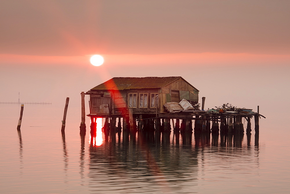 Old fishermen's shack at sunset in Venetian lagoon off the coast of Pellestrina, Venice, Veneto, Italy