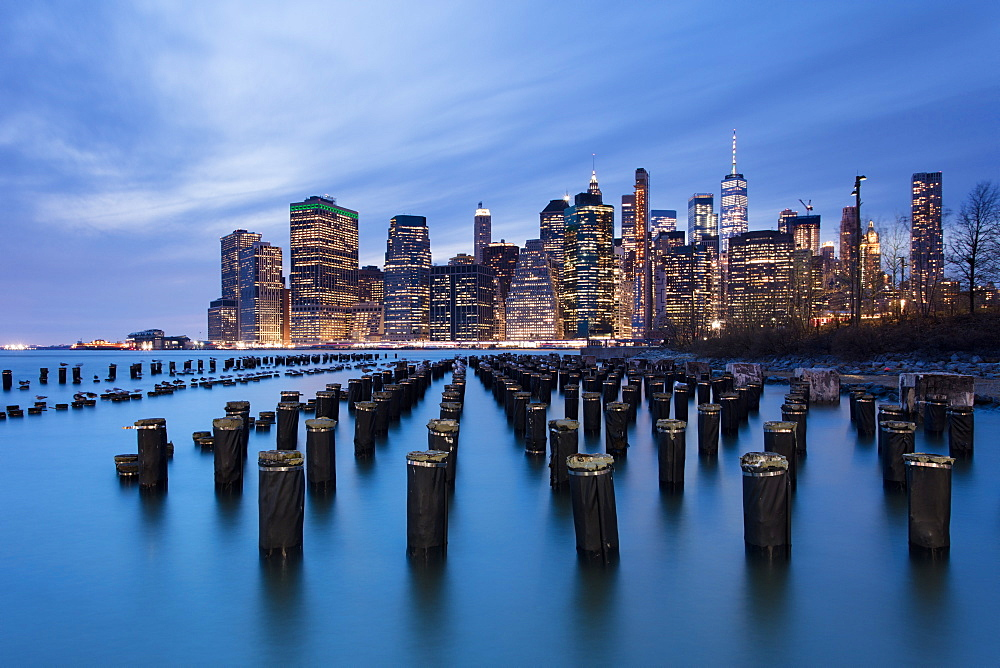 Lower Manhattan skyline with wooden posts from an old pier in the foreground. New York City, New York, United States of America, North America