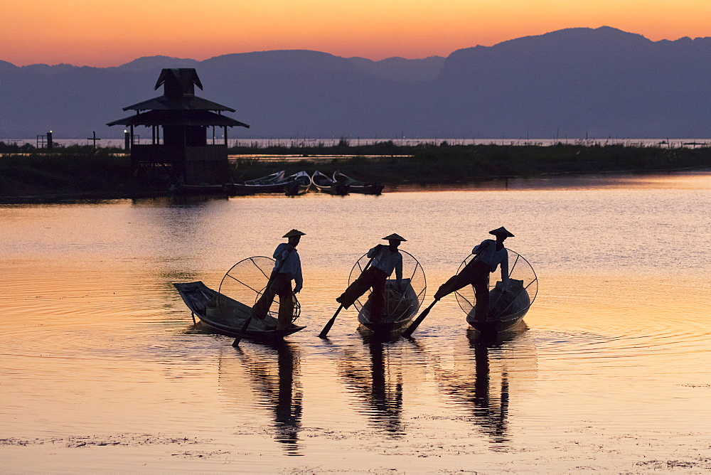 Three fishermen balance on one leg at sunset on Inle Lake, Shan State, Myanmar (Burma), Asia