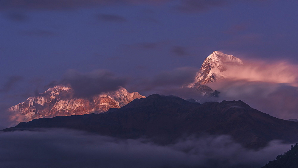 The clouds gradually clearing to reveal the evening light on Annapurna South, viewed from Poon Hill, Himalayas, Nepal, Asia