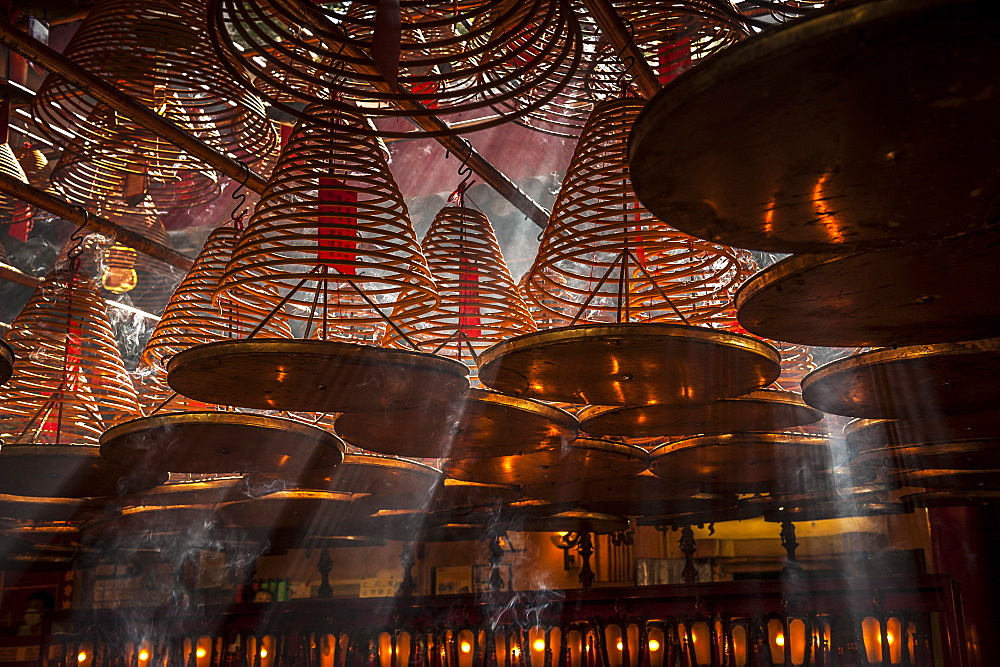 Beams of light streaming into Man Mo Temple past the large incense coils hanging from the ceiling of the Temple, Hong Kong, China, Asia - 1287-56