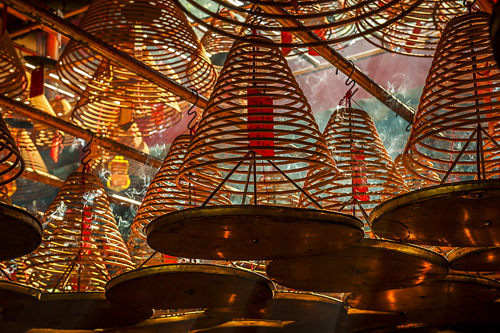 Beams of light streaming into Man Mo Temple past the large incense coils hanging from the ceiling of the Temple, Hong Kong, China, Asia - 1287-57
