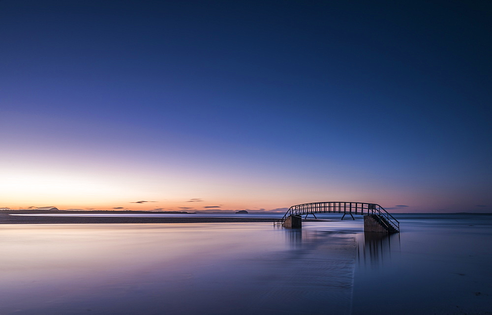 Known as The Bridge To Nowhere, bridge over Biel Water where it flows into Belhaven Bay and the North Sea at Dunbar at sunset, East Lothian, Scotland, United Kingdom, Europe - 1287-59