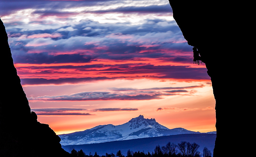 A rock climber scales a wall while the sun sets over a mountain in the distance, United States of America, North America