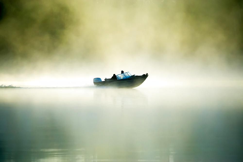 A motorboat navigates the fog on a Minnesota Lake during an early morning, Minnesota, United States of America, North America