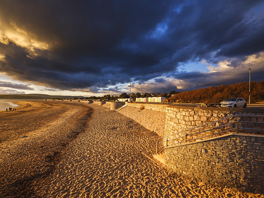 Under dramatic clouds, strong warm sunlight illuminates the beach and sea defences on the sea front at Exmouth, Devon, UK