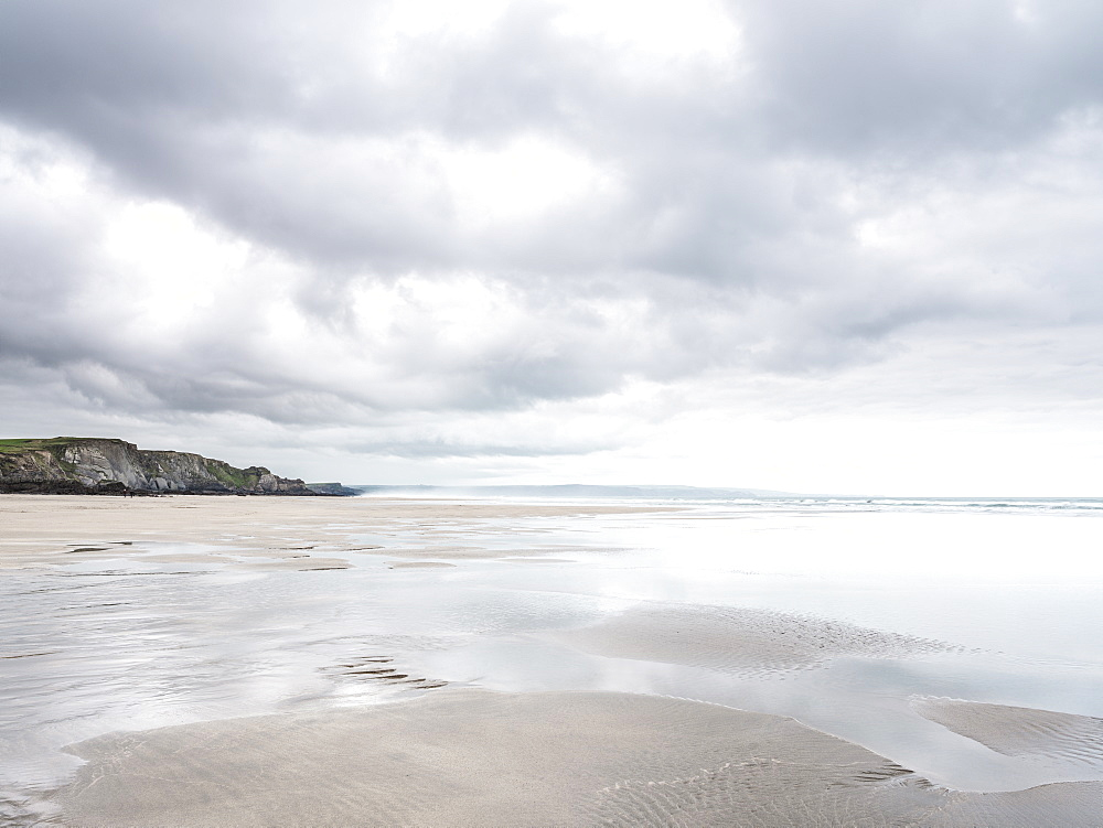 Cloud formations and wet sand on the vast expanse of beach at Sandymouth, looking towards Bude, Cornwall, England, United Kingdom, Europe