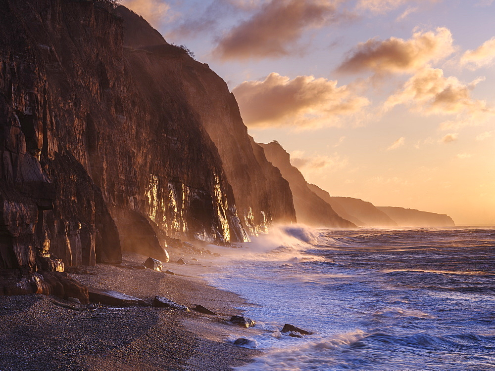 Spray from a storm blows up the cliffs at dawn in the seaside town of Sidmouth, Devon, UK