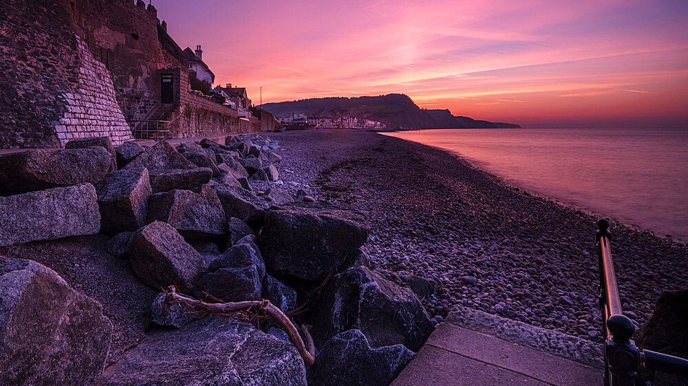 Vivid dawn twilight looking along the beach at the picturesque seaside town of Sidmouth, Devon, UK