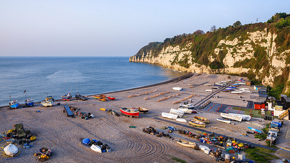 Fishing boats and deckchairs on the popular pebbled beach at Beer near Seaton, Devon, UK - 1295-220