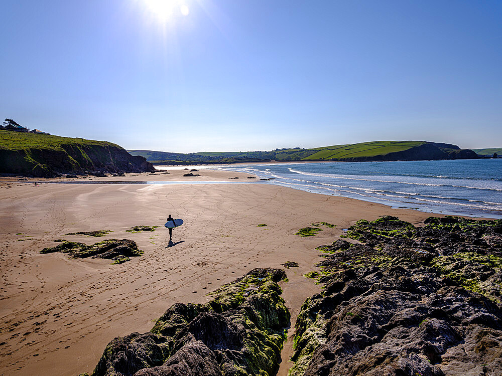 A surfer walks towards his session on sunny morning at Bigbury-on-Sea, Devon, UK. - 1295-226