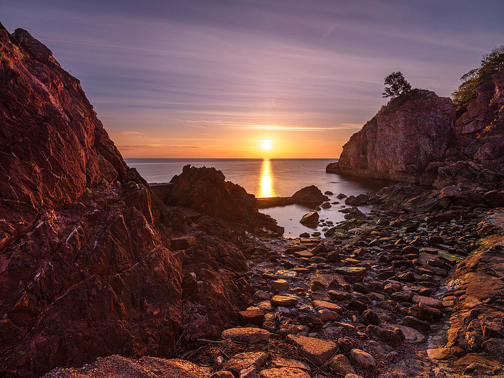 A colourful sunrise over Torbay with warm light on rocks, Babbacombe, Torquay, Devon, UK - 1295-232