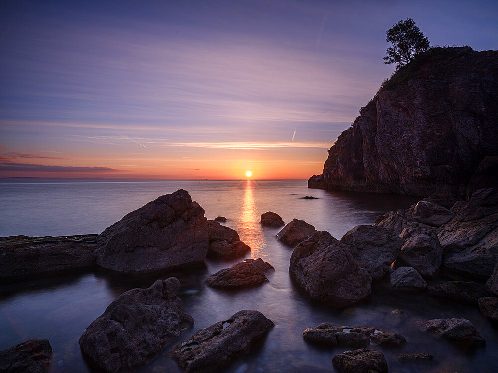 A colourful sunrise over Torbay with warm light on rocks, Babbacombe, Torquay, Devon, UK - 1295-235
