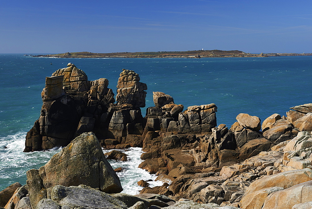Granite rocks on a headland near Old Town, looking at Samsom St Mary's Isles of Scilly, UK
