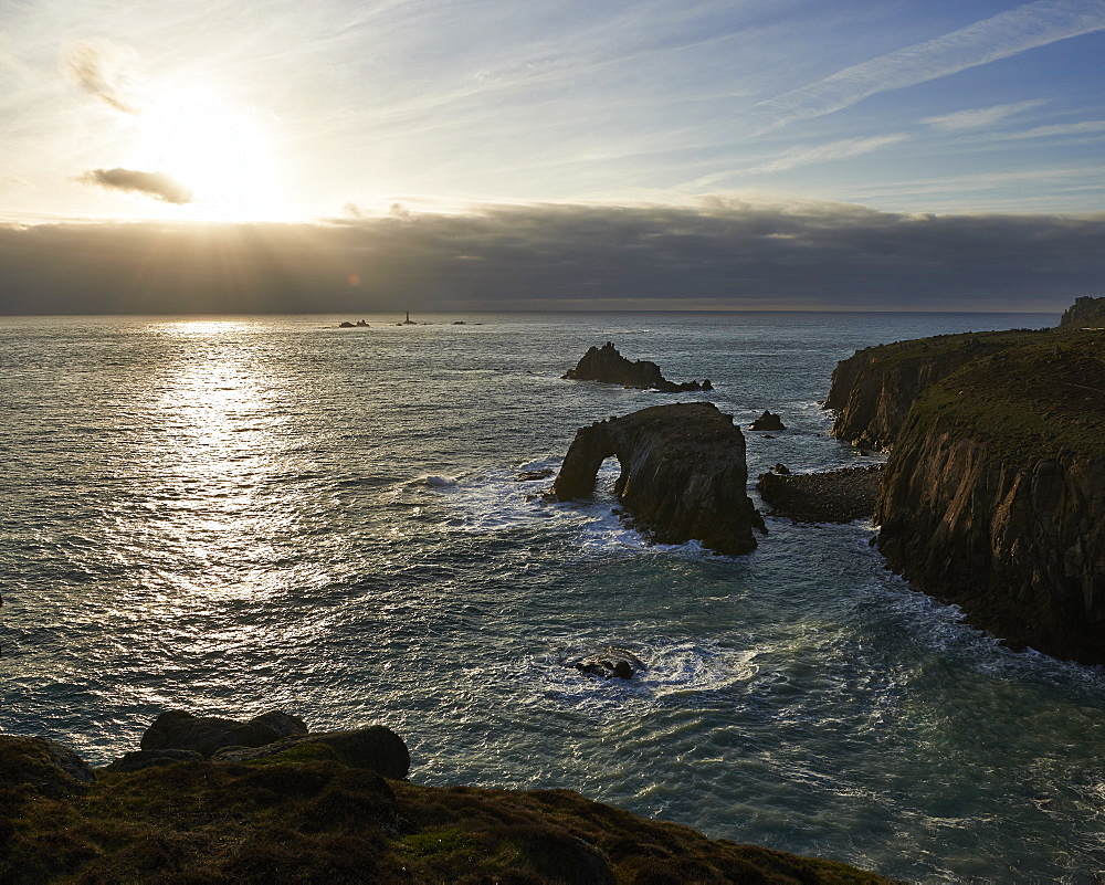 Sunset at Land's End over Enys Dodman rock arch, Longships Lighthouse, Cornwall, UK