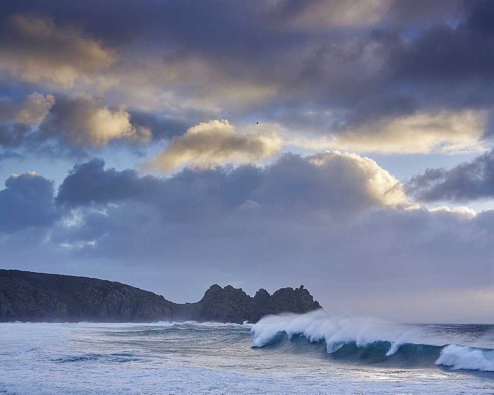 Huge surf looking out towards Logan Rock at Porthcurno, Cornwall, UK