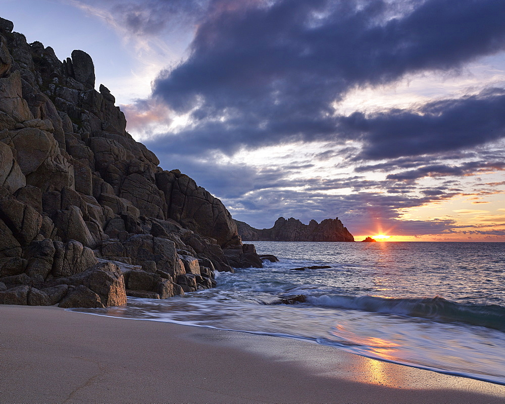 Early morning on the beach looking out towards Logan Rock at Porthcurno, Cornwall, UK
