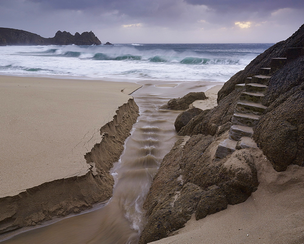 Stormy conditions on the beach looking out towards Logan Rock at Porthcurno, Cornwall, UK