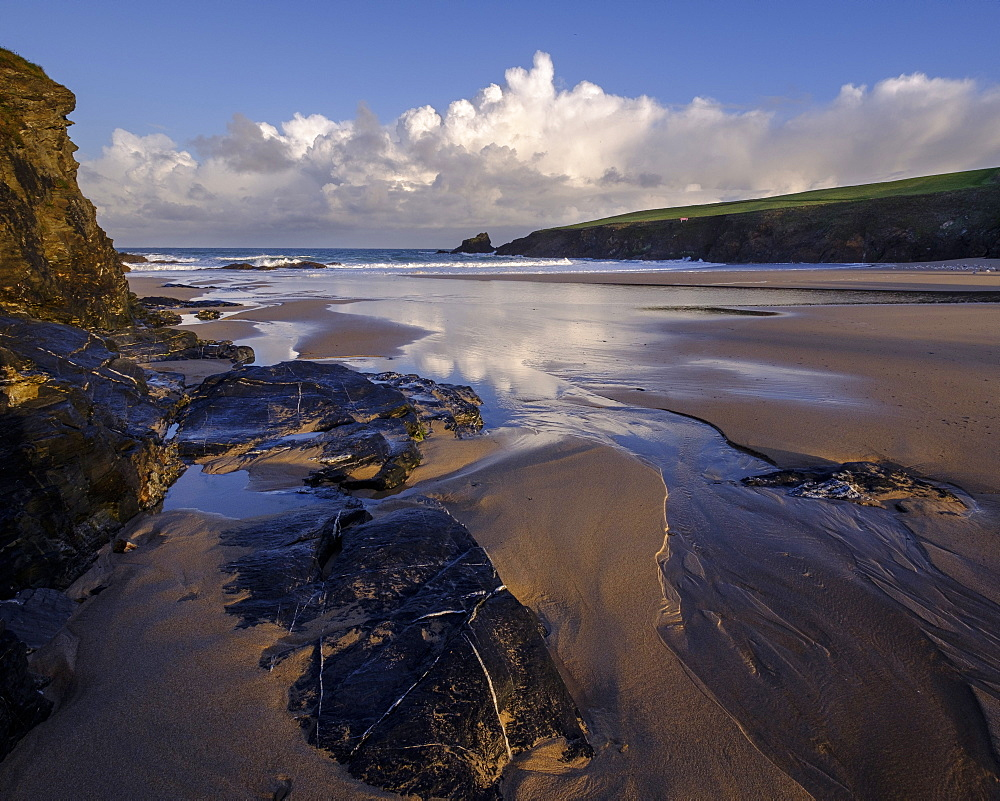 Atlantic clouds reflect dawn light onto the wet sands and rocks of Trevone, near Padstow, Cornwall, UK