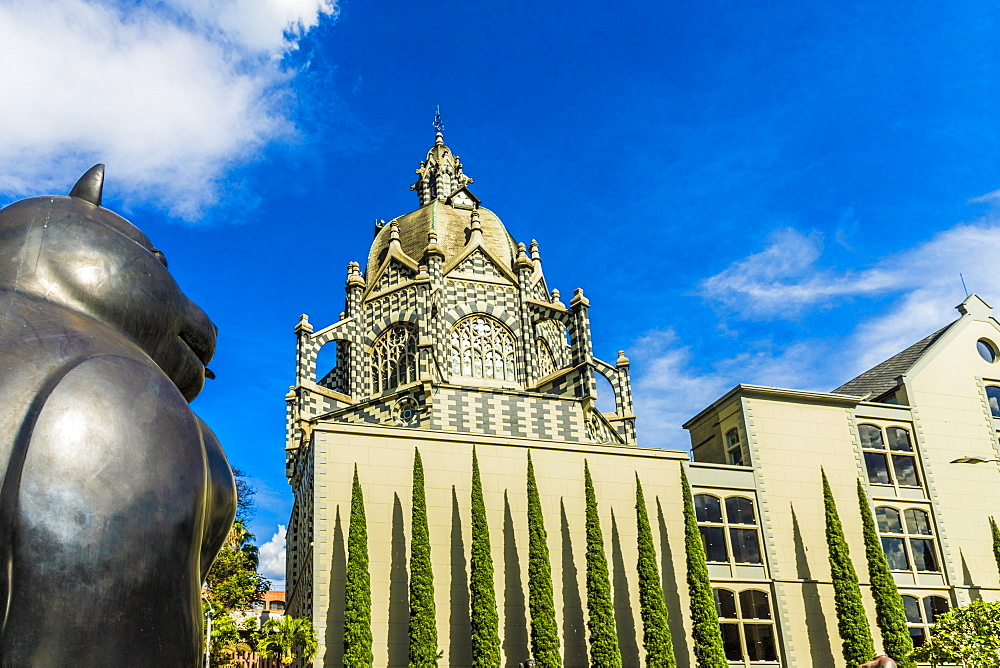 A view of the Rafael Uribe Uribe Palace of Culture with the Fernando Botero statue Gato (Cat) in the foreground, Medellin, Colombia, South America