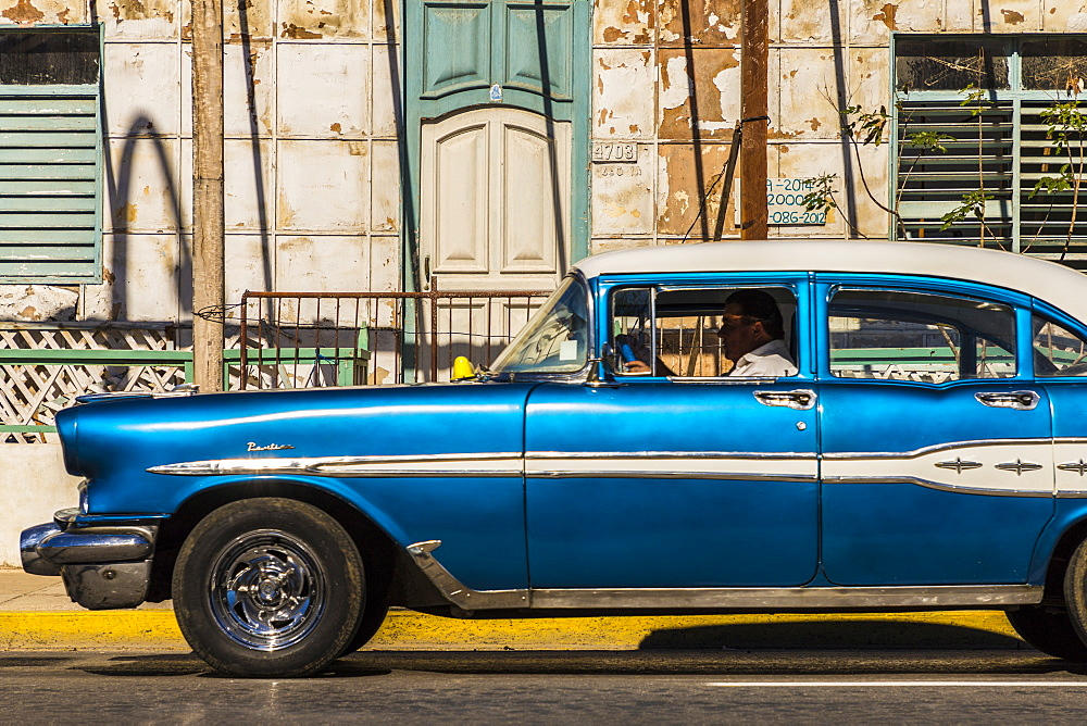 A classic American car driving past an old building in Varadero, Cuba, West Indies, Caribbean, Central America