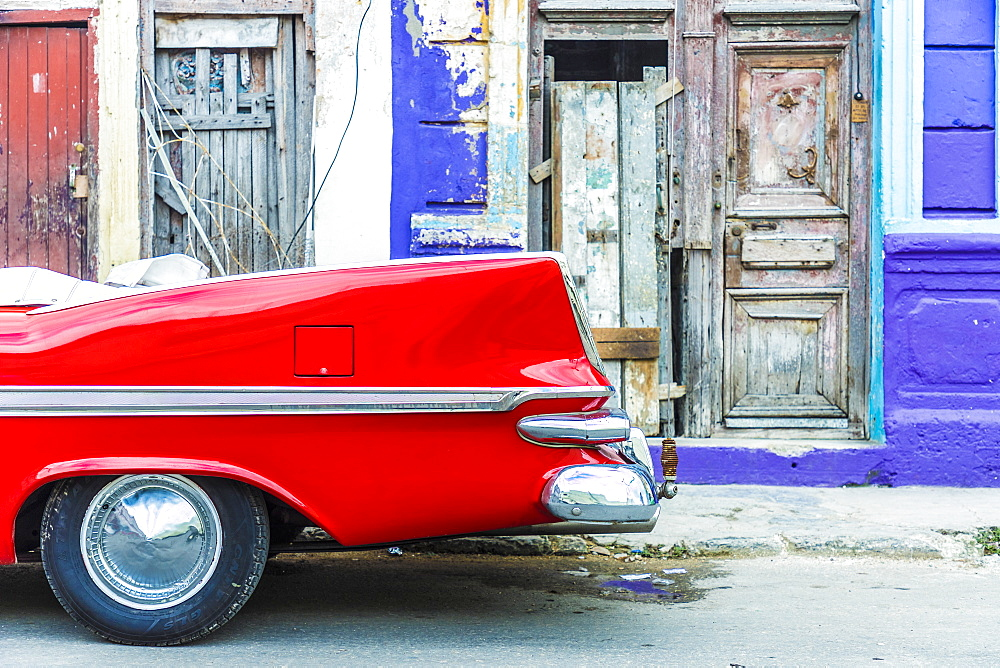 A red vintage car parked against colourful local architecture in Havana, Cuba, West Indies, Caribbean, Central America