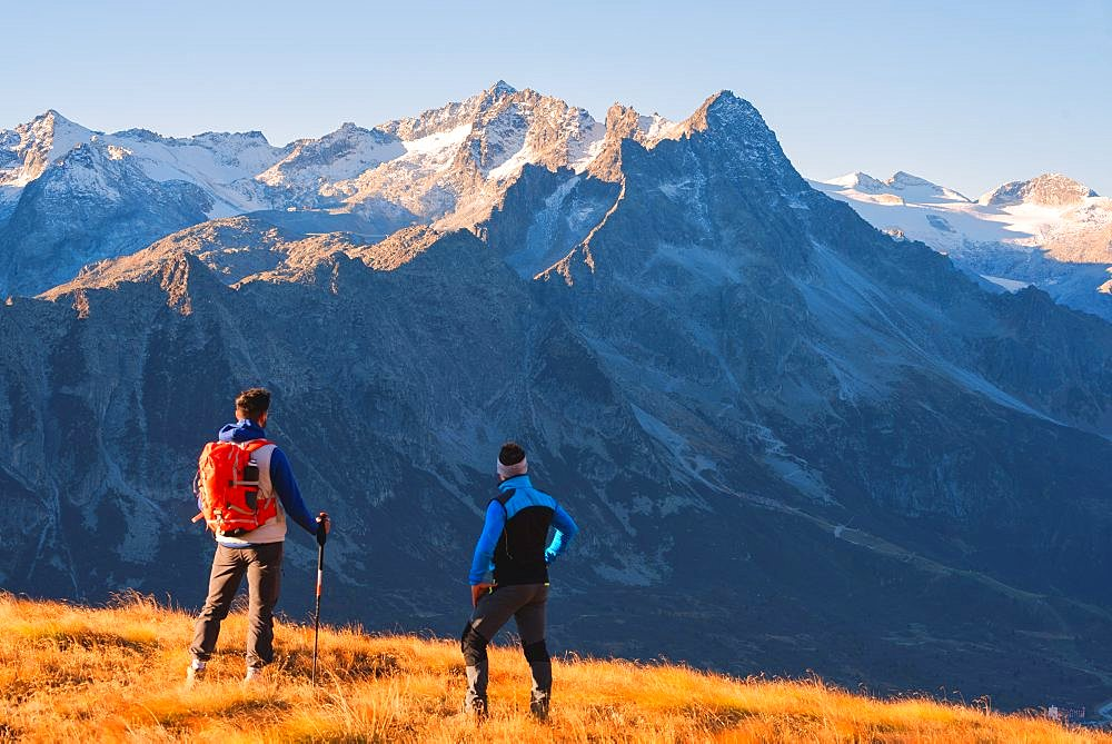 Hikers admiring the mountains in Autumn Season in Stelvio National park in Brescia province, Lombardy district, Italy, Europe.