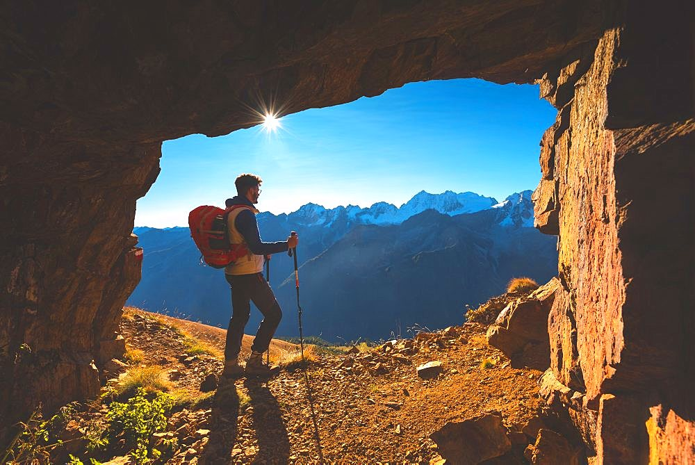 Hiker in a Mountain cave in Autumn Season in Stelvio National park in Brescia province, Lombardy district, Italy, Europe.
