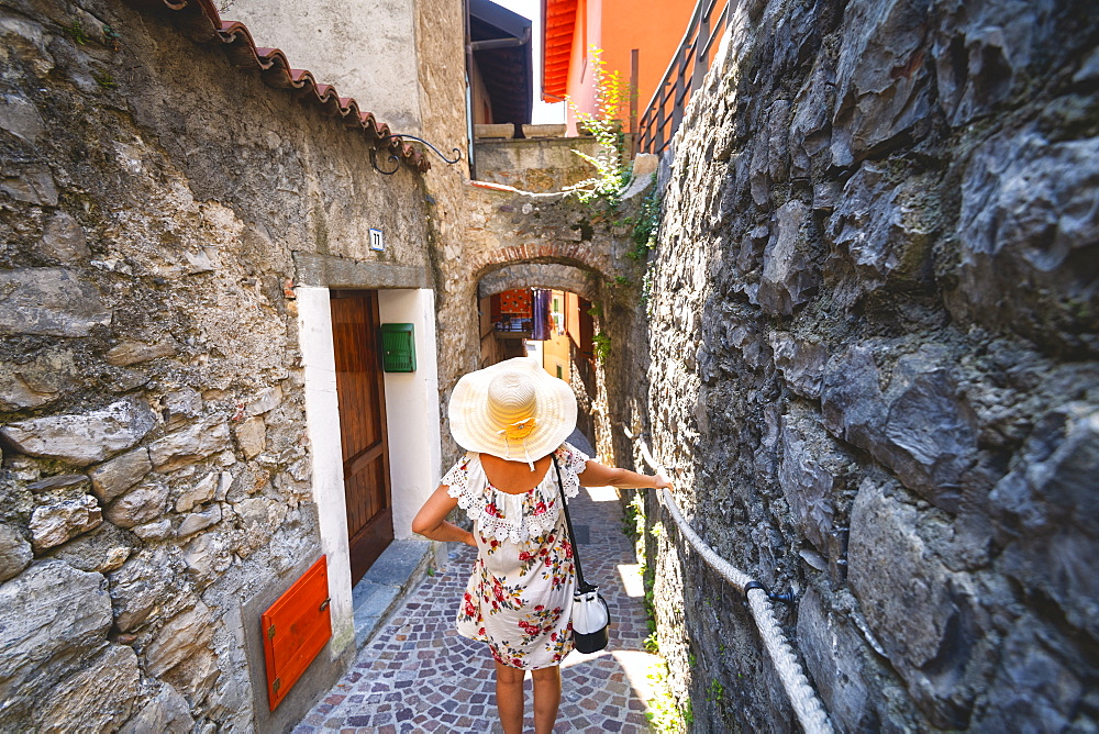 Woman lost in the alleys in Monte Isola on the Iseo Lake, the largest lake island in Europe, Province of Brescia, Lombardy, Italy, Europe