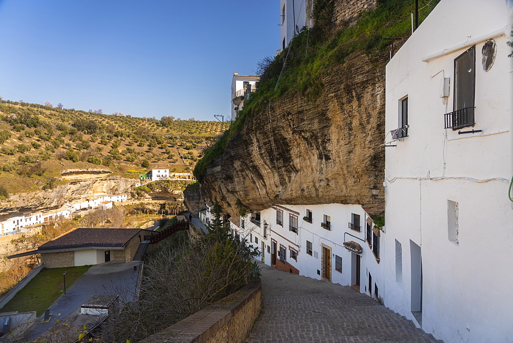 Setenil de las Bodegas in the province of Cadiz, with its white historic buildings and the houses under the rock mountain - 1300-204