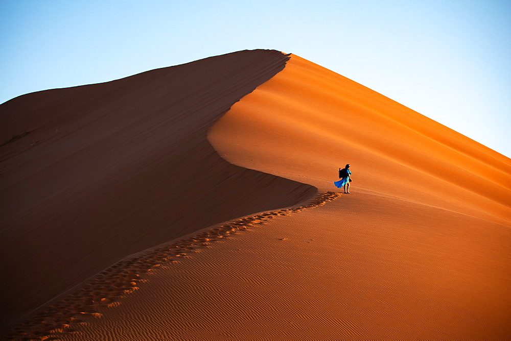 Shot of model Climbing Dune 13 with photography gear, Sossusvlei, Namibia, Africa - 1304-48