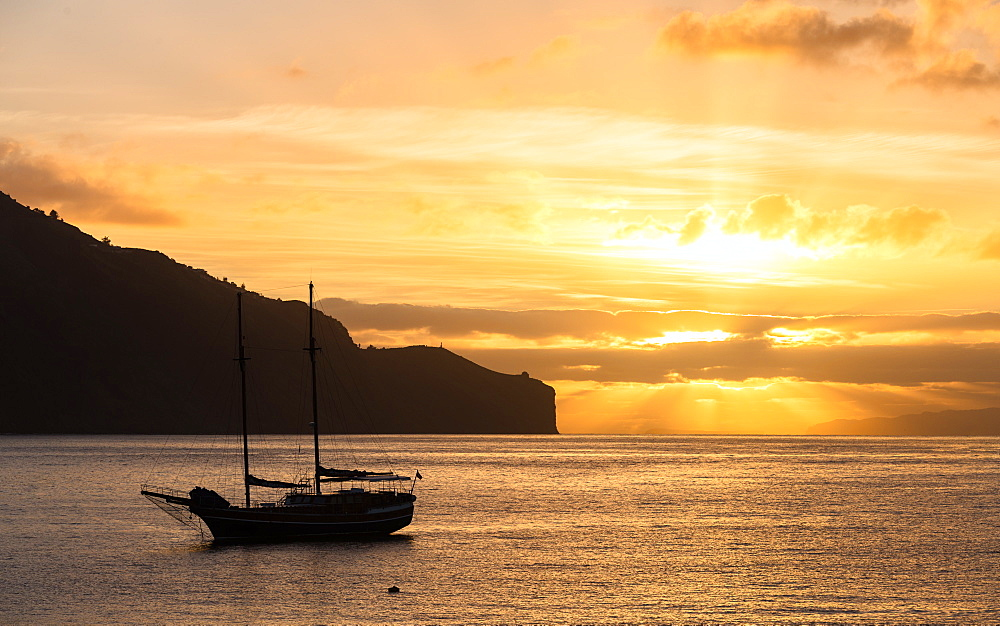 boat on the bay of Funchal city at sunrise.