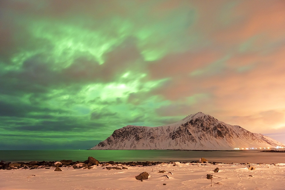 The Northern Lights (Aurora borealis) with mountain range in winter, Reine, Lofoten Islands, Nordland, Arctic, Norway, Europe