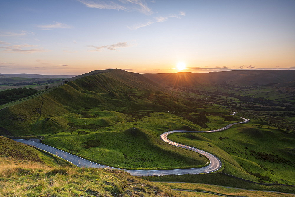Long and winding rural road leading through green hills in the Peak District, with Rushup Edge, Peak District National Park, Derbyshire, England, United Kingdom, Europe