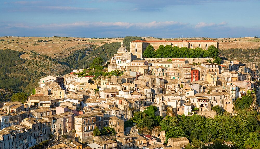 View over the sunlit rooftops of Ragusa Ibla, evening, houses clinging to steep hillside, Ragusa, UNESCO World Heritage Site, Sicily, Italy, Europe