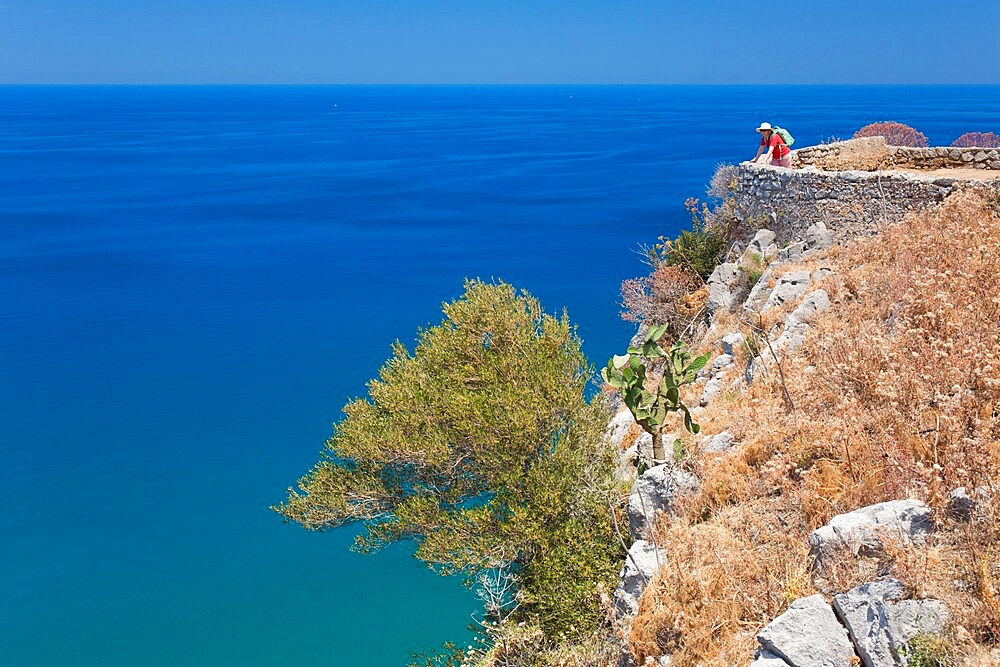 Lone visitor admiring view over the Tyrrhenian Sea from summit of La Rocca, Cefalu, Palermo, Sicily, Italy