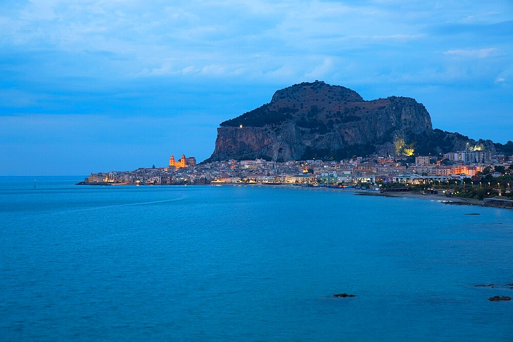 View along coast to the town and illuminated cathedral, dusk, La Rocca towering above, Cefalu, Palermo, Sicily, Italy - 1310-136